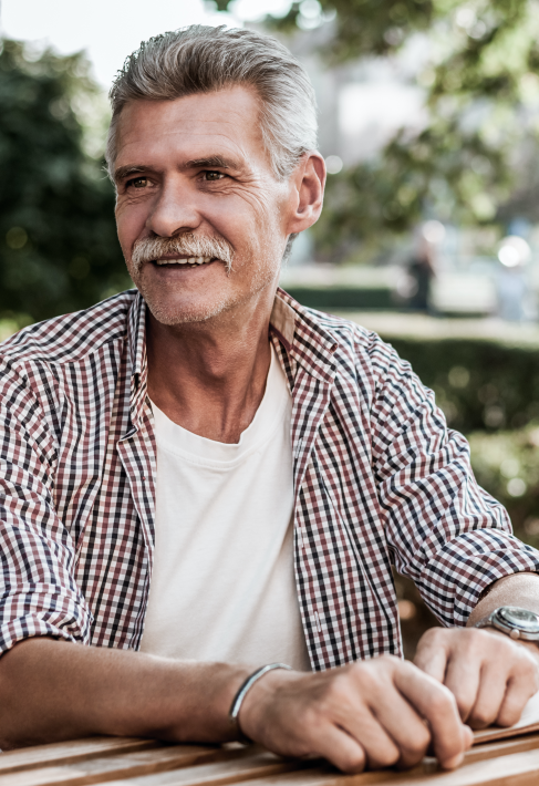 older man sitting on a bench in an outdoor area